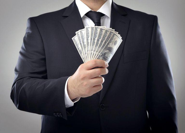 Businessman holding a stuck of money