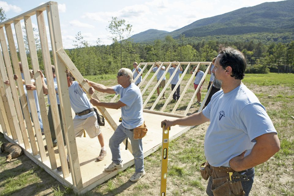 Volunteers raising the framing of a house.