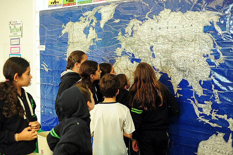Mexico, Mexico City, children looking at large wall world map