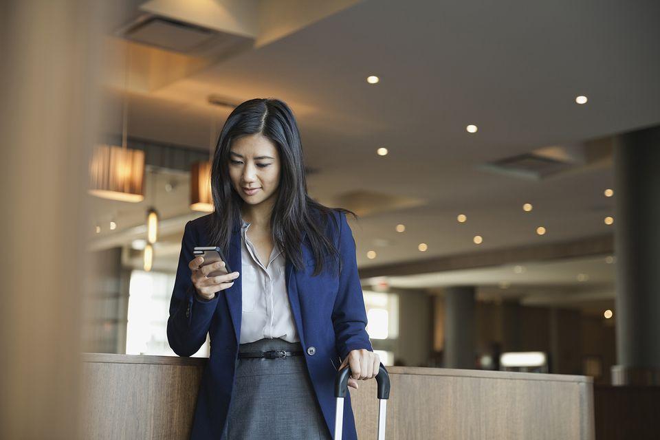 Businesswoman using smart phone in hotel lobby.