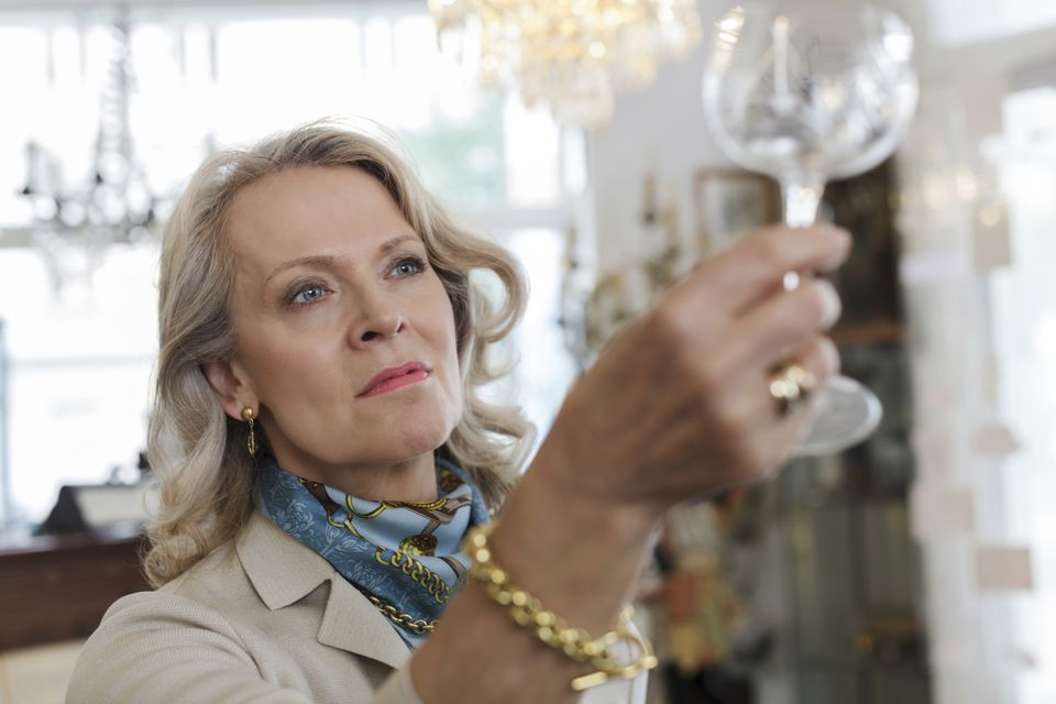 woman looking at antique glass at estate sale