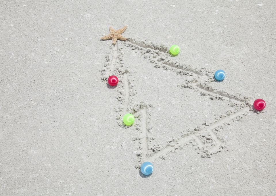 Christmas tree etched in beach sand with star fish and ornaments.