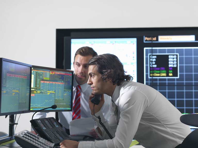 Financial traders in front of computer monitors.