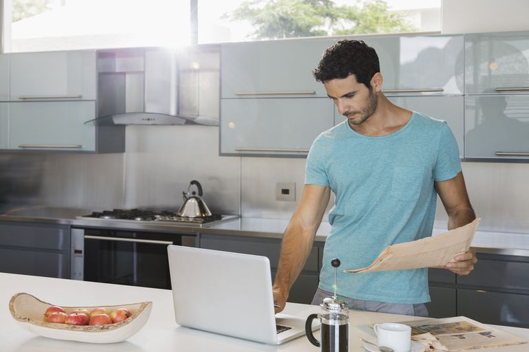 Man with newspaper using laptop in kitchen