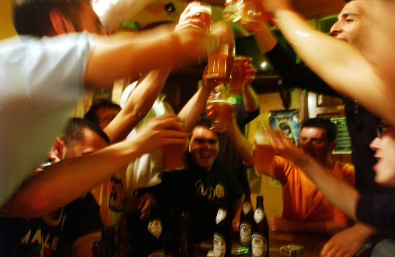 young men drinking beer and cheering