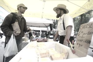 NEW YORK - OCTOBER 02: Amish farmer John Stoltzfoos (R) talks with a customer at the Union Square farmers market October 2, 2009 in New York City. Over the past decade, neighborhood farmers markets have increased 71 percent in the U.S., where consumers can purchase items from local producers.