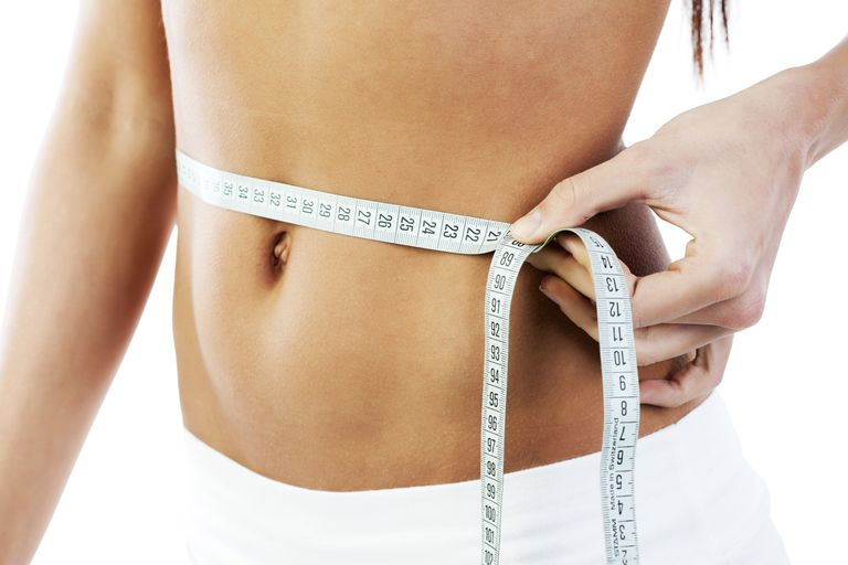 woman with measuring tape around abs