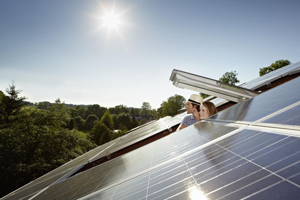 Couple peering out of solar panel roof
