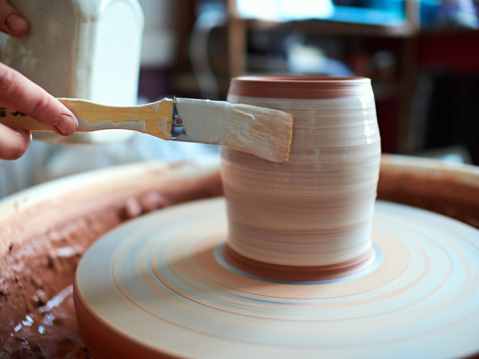 production process of pottery. Application of glaze brush on ceramic ware.