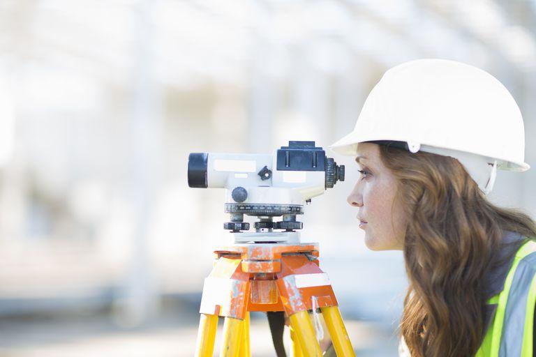 A surveyor looks through level on construction site