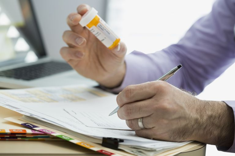 doctor writing prescription for medication with pill bottle in hand