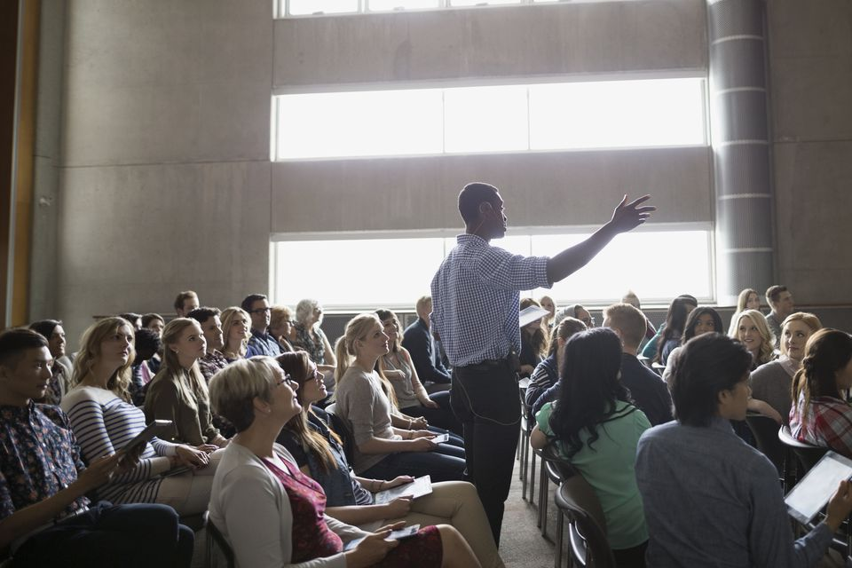 Professor giving lecture among auditorium audience