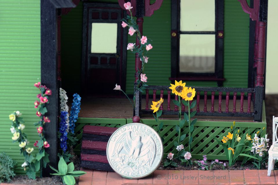 Detailed quarter or O scale flowering plants decorate a dolls house or railway house.