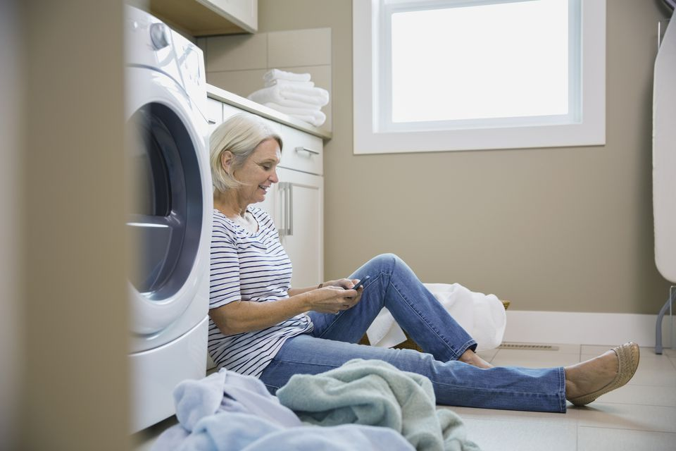 Woman texting on laundry room floor