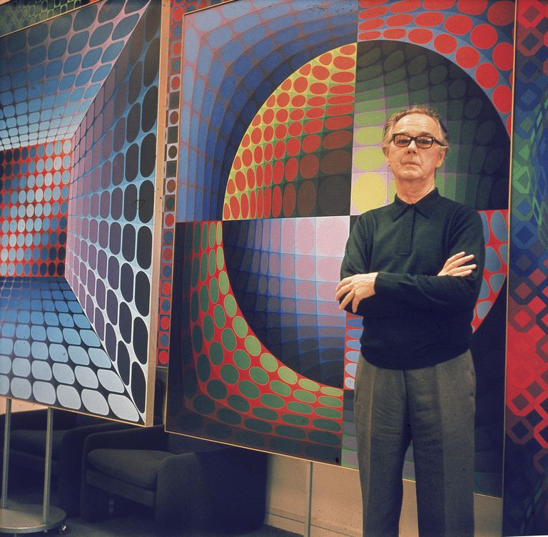 Hungarian born French artist Victor Vasarely (1908 - 1997) poses in front of one of his Op Art paintings