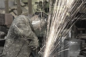 U.S. Army Spc. Brian Kilough, a metal worker, and native of Temple, Texas, assigned to 4th Support Battalion, Fort Hood, Texas, Multi-National Division-Baghdad, grinds a stack of metal sheets using a circular grinder, on Jan. 25, 2009, at Forward Operations Base Falcon, Baghdad, Iraq.