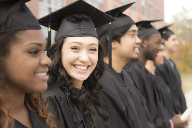 Educaton: Graduates stand in row on college campus.