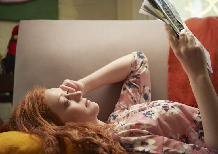 Young woman lying on sofa at home reading magazine