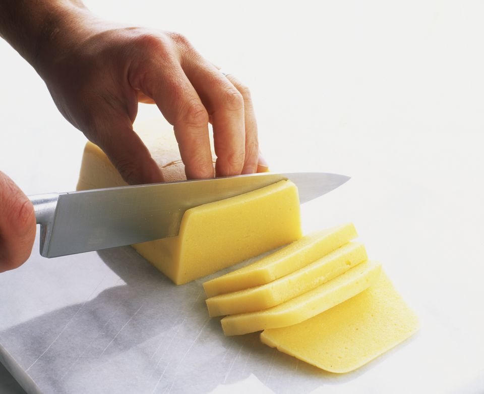 Block of cooked cooled polenta being sliced.