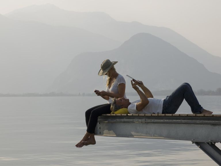A couple relazing on a jetty above a lake