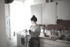 Smiling woman texting with cell phone in kitchen