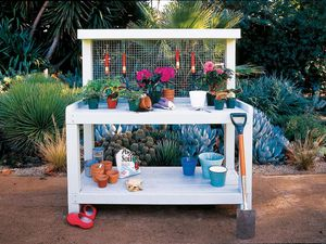 A white wooden potting bench with gardening supplies