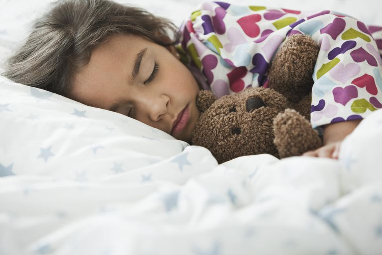 Mixed race girl sleeping in bed with teddy bear