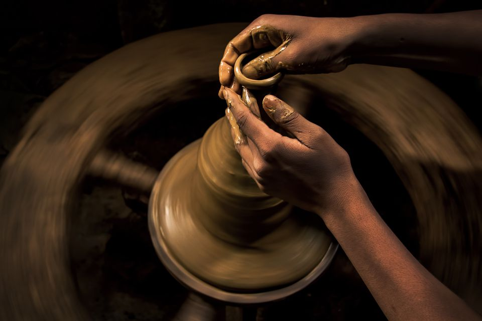 A potter gives finishing touches to a clay lamp