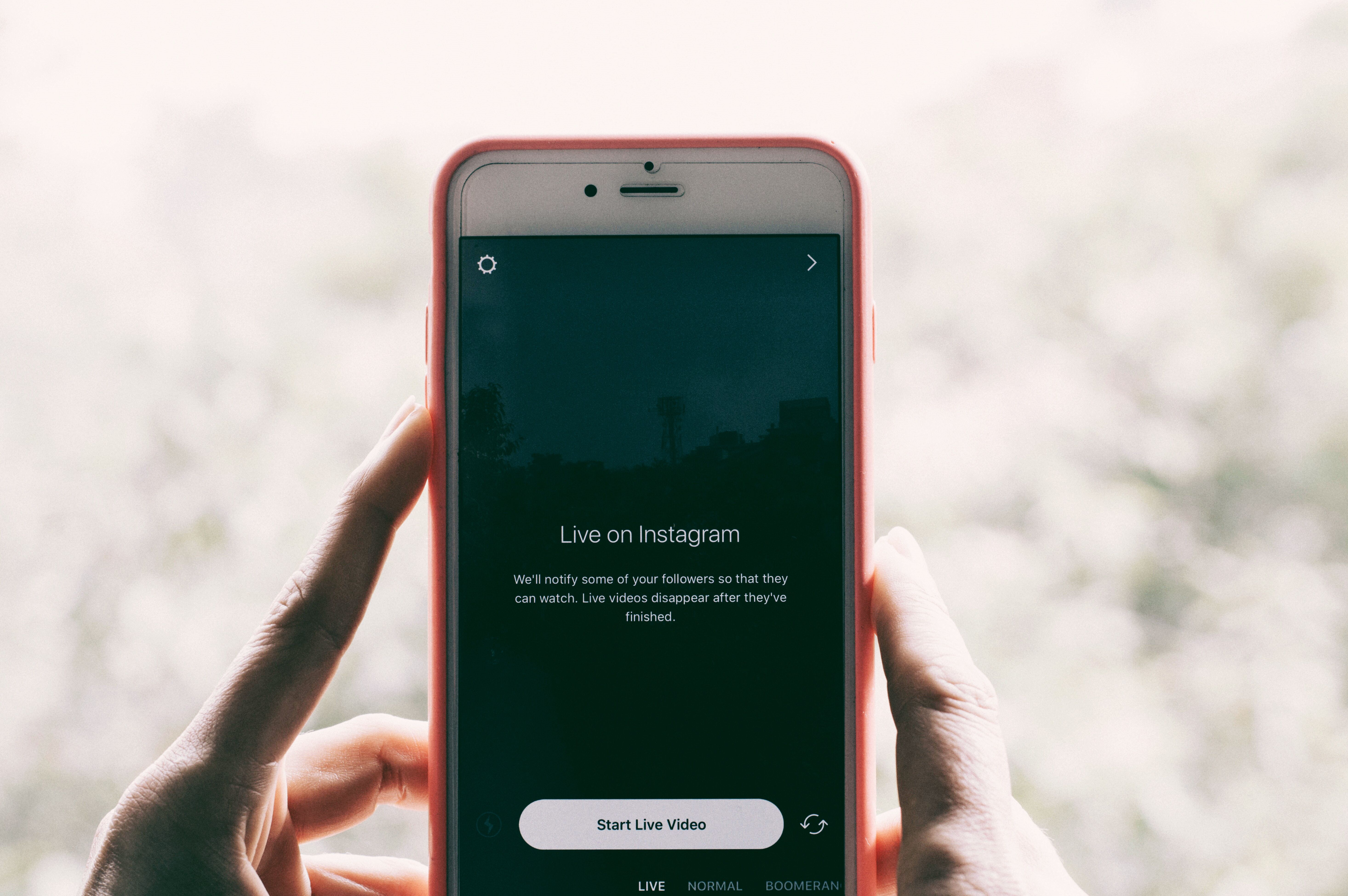 An image of a person holding up a smartphone and getting ready to go live on Instagram.