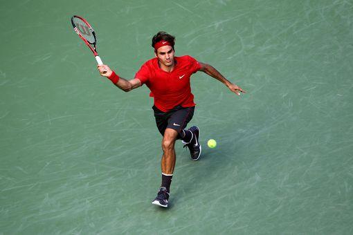 Roger Federer hits a forehand return against Novak Djokovic of Serbia during Day Thirteen of the 2011 US Open