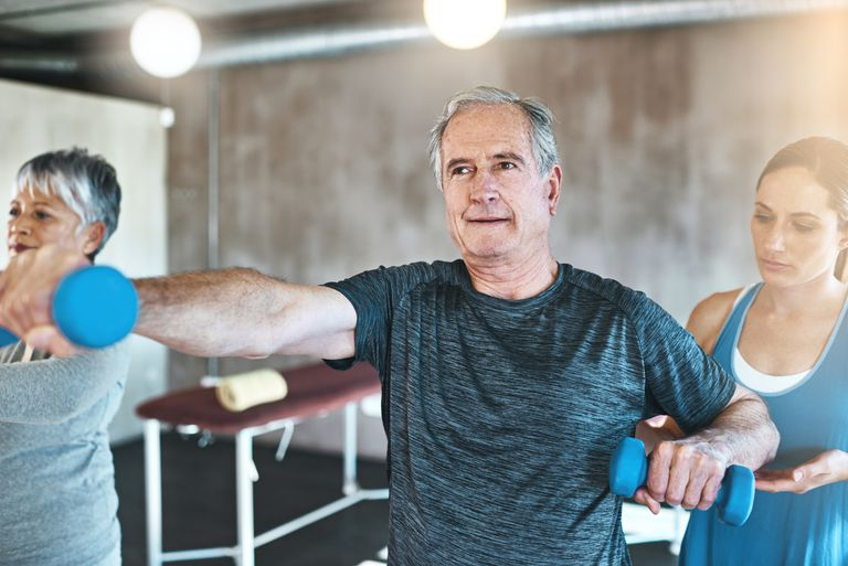 Older man using dumbbells in an exercise class