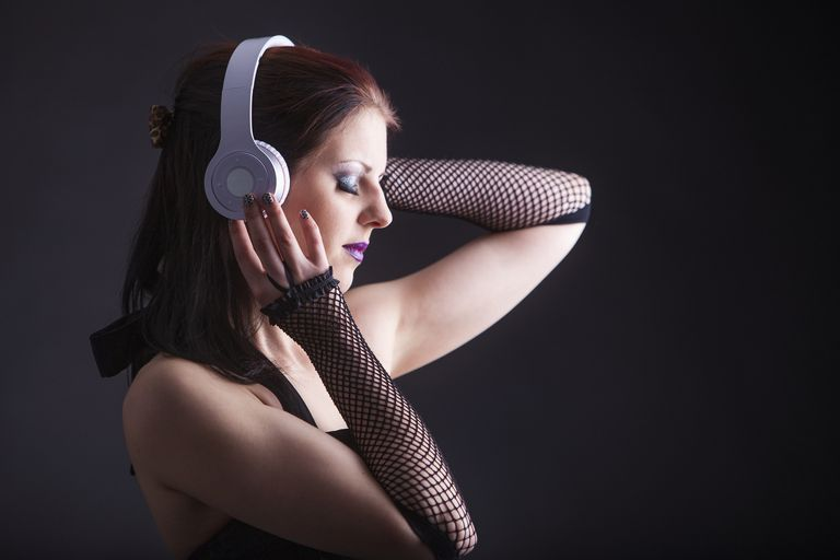 Woman listens to music using Bluetooth headphones