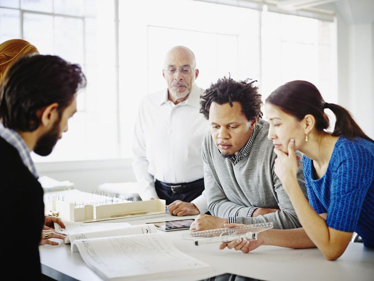 Group of coworkers examining project in office