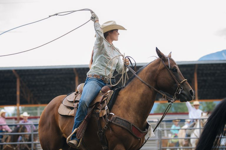 Cowgirl twirling lasso in rodeo