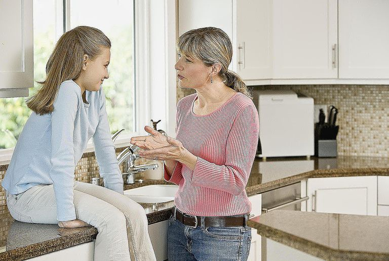 Mother and daughter (10-11) discussing in kitchen.