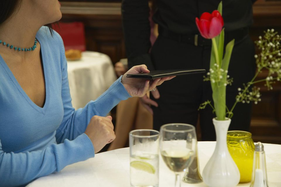 Woman paying bill in restaurant,
