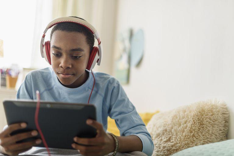 Black boy in headphones using digital tablet