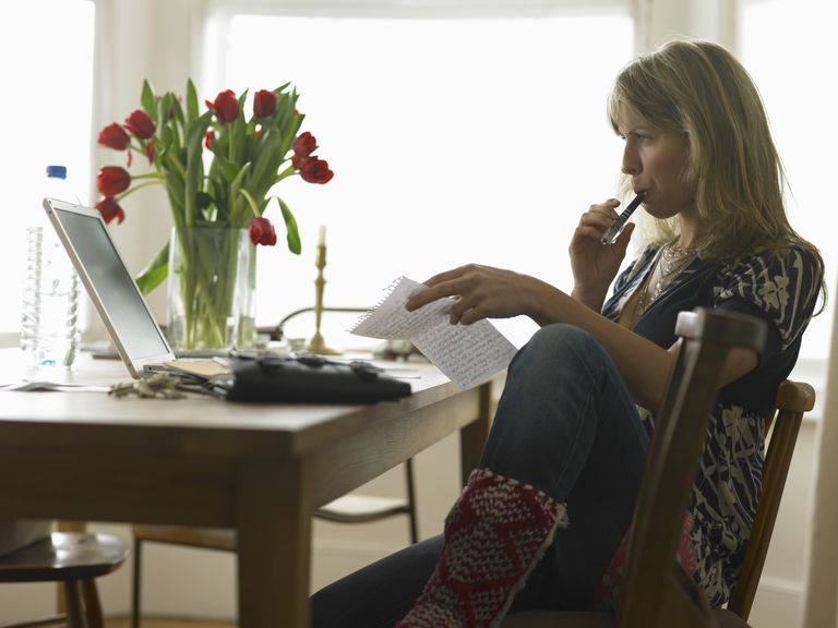 Young woman sitting at laptop on dining table holding sheet of paper and writing her resignation letter.