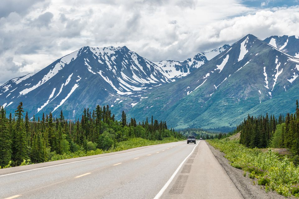 Smooth Alaskan highway leading towards mountains in summer