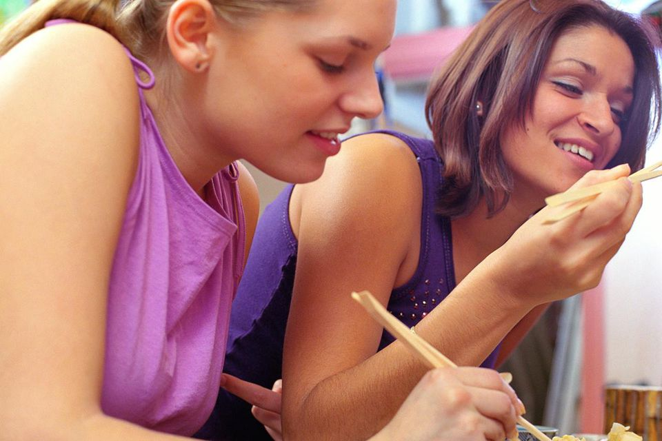Two young women eating with chopsticks, close-up