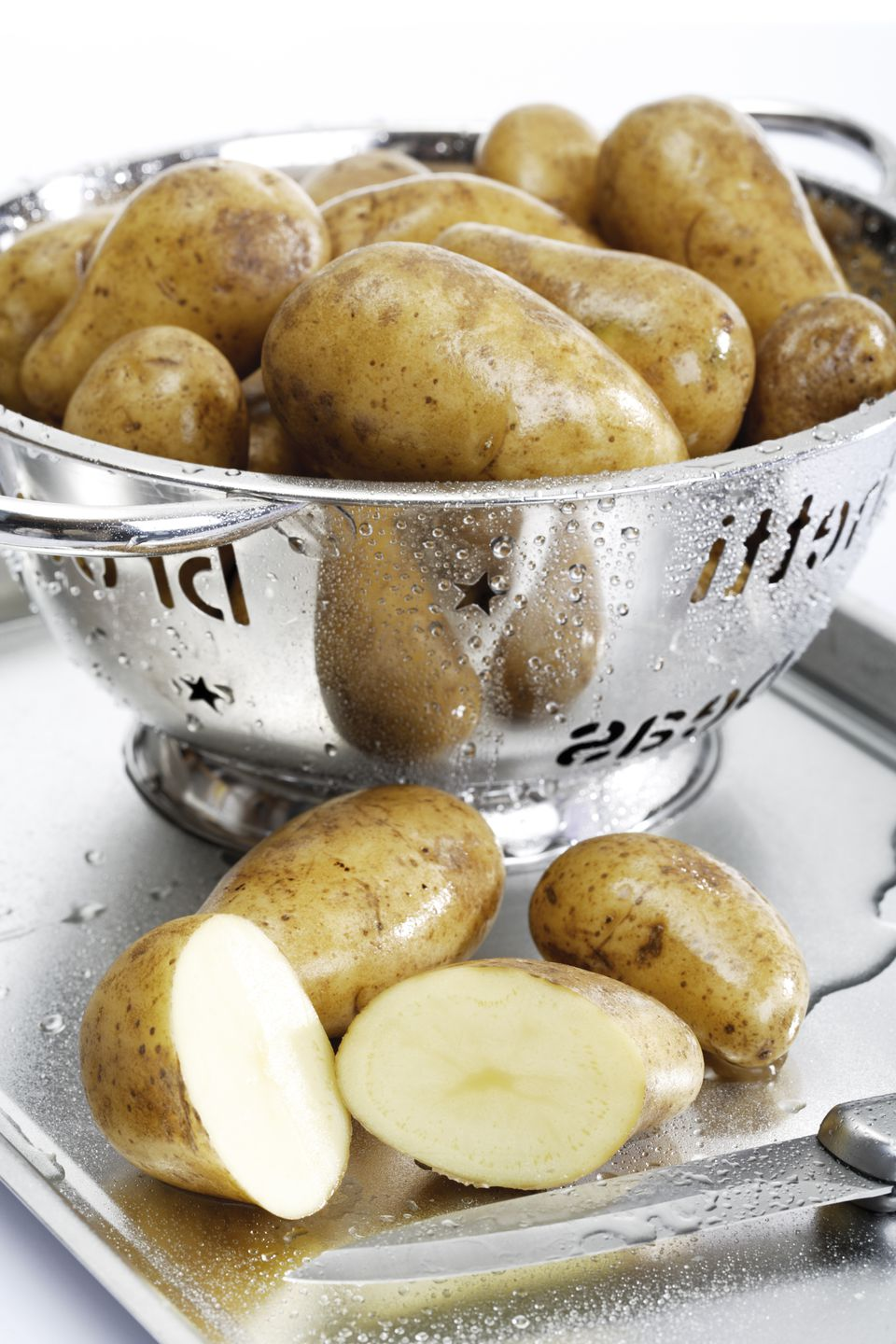 Raw potatoes in colander, close-up