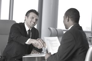 Man interviewing another man with resume in hand