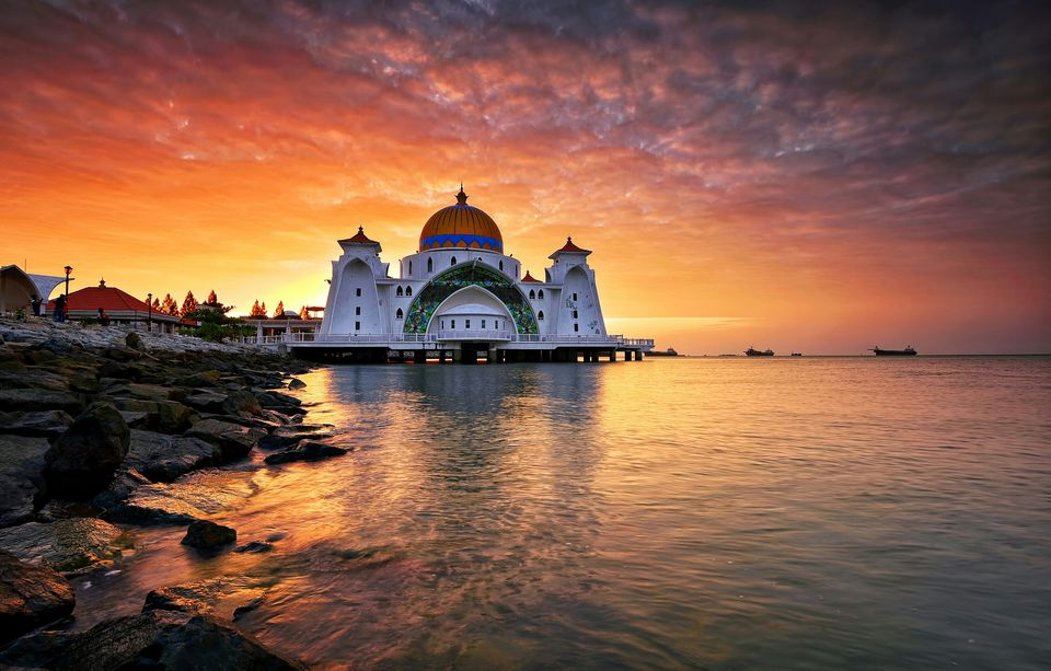 Malacca Straits Mosque By Sea Against Orange Sky During Sunrise