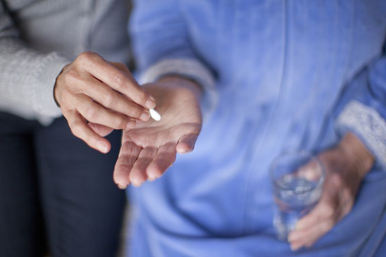 A woman taking a pill with a glass of water.