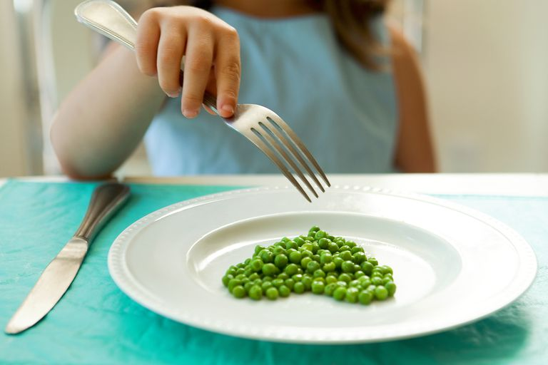 Girl eating green peas with a fork