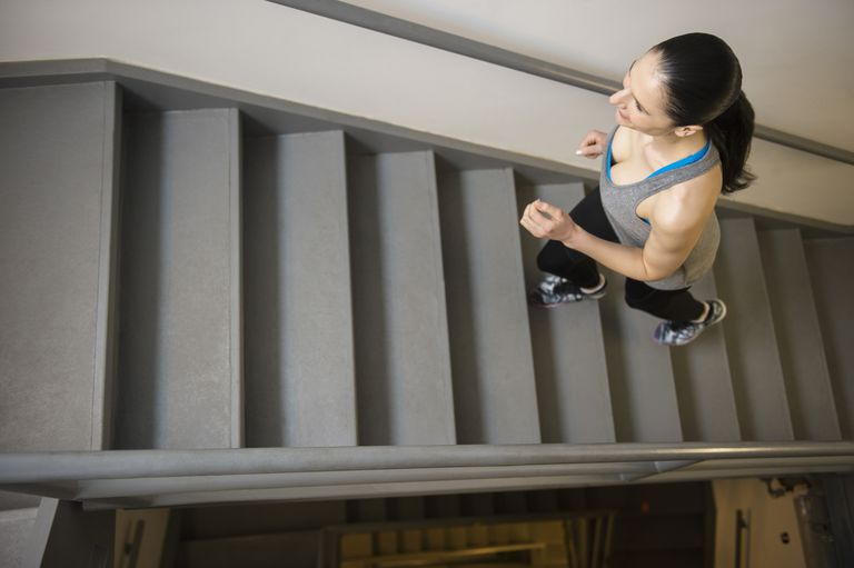 Woman running up the stairs inside apartment building