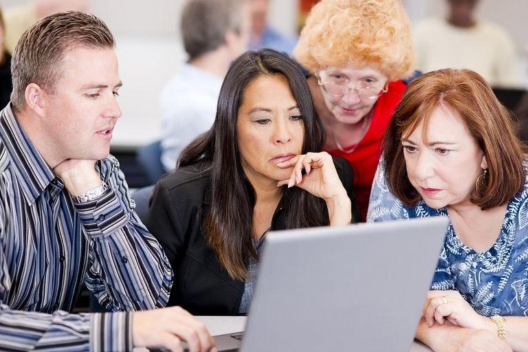 mature students gathered around a laptop
