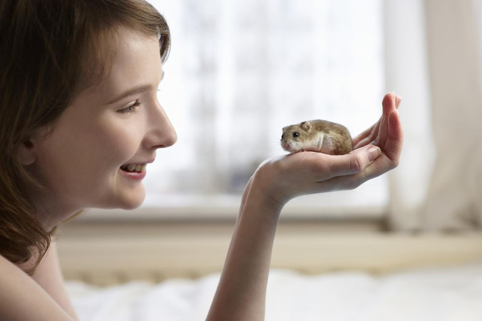 Young woman holding hamster in hand.