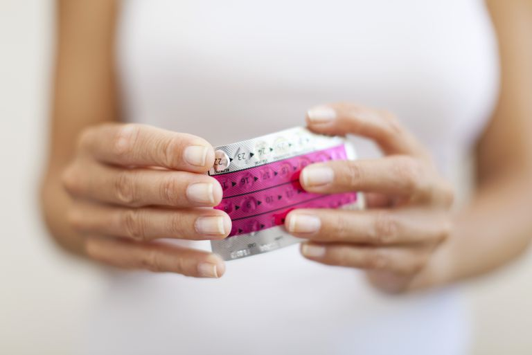 woman popping out birth control pill out of blister pack