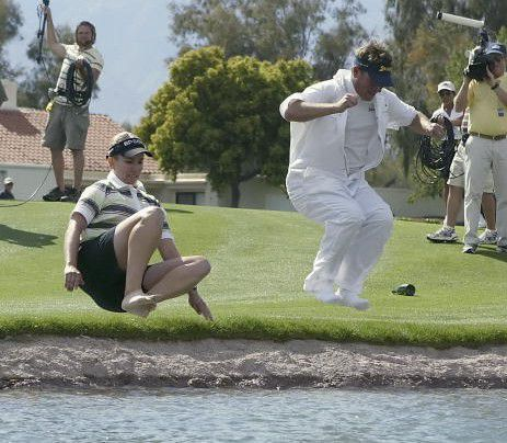 female golfer and her caddie jumping in a lake